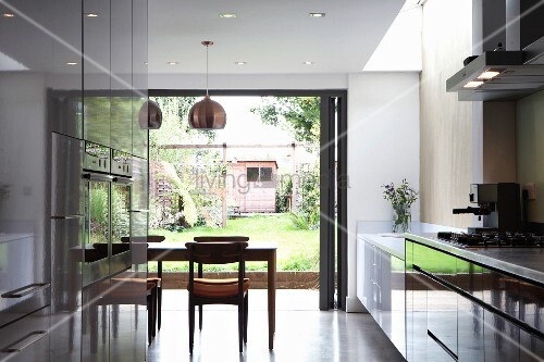 offene k che mit gl nzender schrankfront und essbereich vor terrassenfaltt r bild kaufen. Black Bedroom Furniture Sets. Home Design Ideas