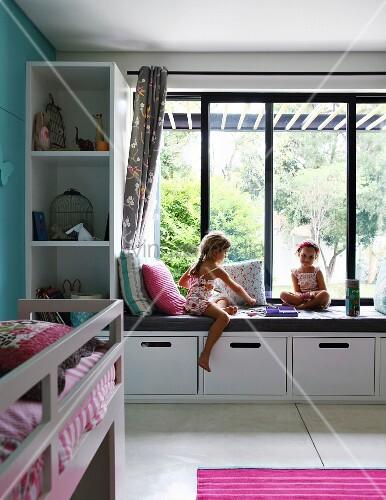 m dchen beim spielen auf eingebauter bank mit polster vor fenster in modernem kinderzimmer. Black Bedroom Furniture Sets. Home Design Ideas