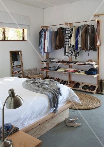kleiderst nder mit ablagen in schlichtem schlafzimmer bild kaufen living4media. Black Bedroom Furniture Sets. Home Design Ideas