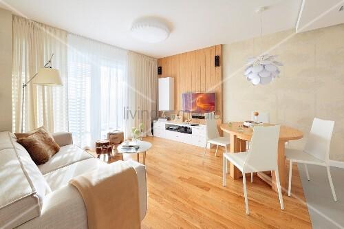 essplatz mit weissen st hlen um holztisch seitlich helles sofa in offenem modernem wohnraum. Black Bedroom Furniture Sets. Home Design Ideas