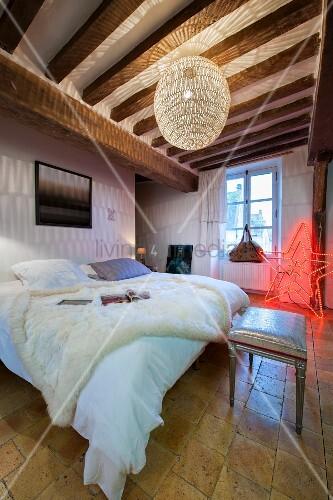 weisses fell auf doppelbett unter kugelleuchte im. Black Bedroom Furniture Sets. Home Design Ideas