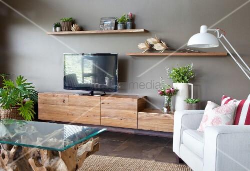 couchtisch mit glasplatte und heller sessel gegen ber lowboard mit rustikalen schrankmodulen. Black Bedroom Furniture Sets. Home Design Ideas