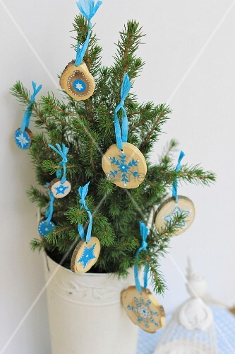 small fir tree in white vintage pot decorated with small wooden discs painted with pale blue. Black Bedroom Furniture Sets. Home Design Ideas