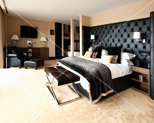 maskulines schlafzimmer mit schwarz gepolstertem betthaupt bettbank und lesesessel bild. Black Bedroom Furniture Sets. Home Design Ideas