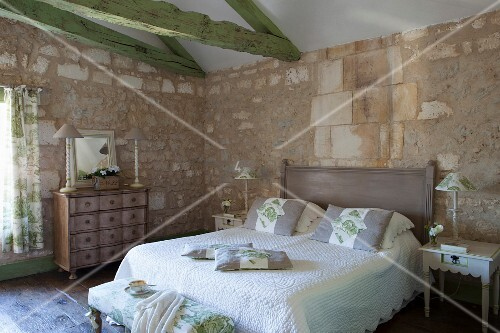 mediterranes schlafzimmer mit natursteinwnden und grn gestrichenen deckenbalken antike kommode und gequiltete tagesdecke - Schlafzimmer Mediterran