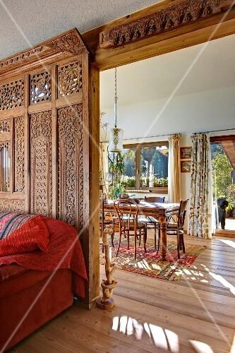 Kunstvoll geschnitzte holzwand als raumteiler zwischen for Sofa als raumteiler