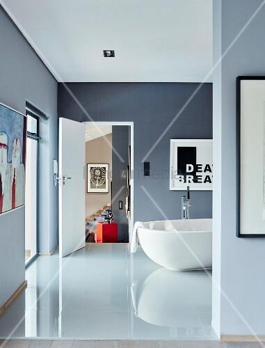 blick durch durchgang auf gl nzenden fliesenboden in blau grauem bad mit freistehender wei er. Black Bedroom Furniture Sets. Home Design Ideas