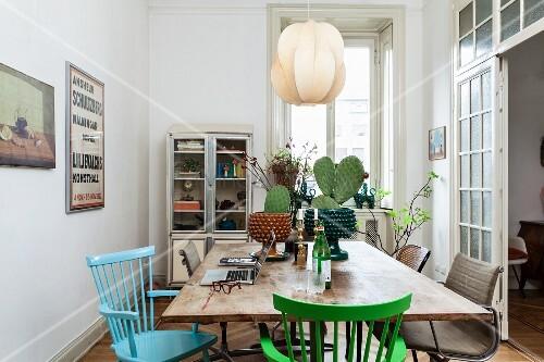 esstisch mit kakteen farbige holzst hle dar ber pendelleuchte mit schirm aus furnierbl ttern. Black Bedroom Furniture Sets. Home Design Ideas