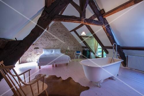 ausgebautes dachgeschoss mit freistehender badewanne doppelbett und rustikalen sichtbalken. Black Bedroom Furniture Sets. Home Design Ideas