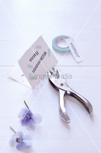 Bastelmaterial für Namenskärtchen: Lochzange, Blüten und Masking Tape