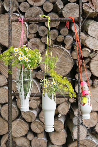 Homemade hanging flower vases made from plastic bottles and string