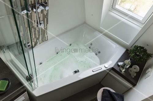 blick auf whirlpool badewanne unter dem fenster in kleinem badezimmer bild kaufen living4media. Black Bedroom Furniture Sets. Home Design Ideas