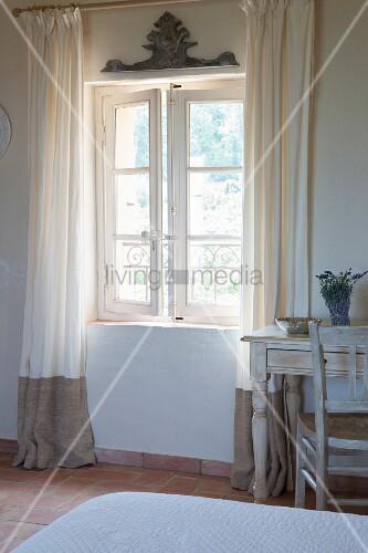 bodenlange vorh nge neben ge ffnetem sprossenfenster und vintage schreibtischplatz im. Black Bedroom Furniture Sets. Home Design Ideas