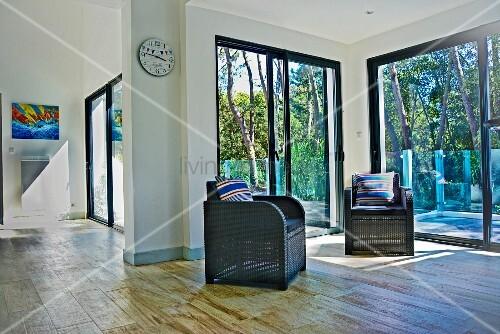 wohnbereich mit zwei dunklen korbsesseln vor terrassent r und gartenblick mit b umen bild. Black Bedroom Furniture Sets. Home Design Ideas