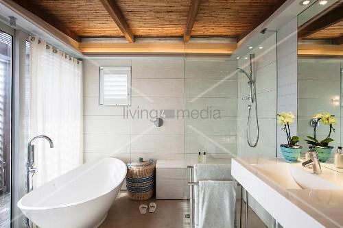 modernes bad mit freistehender wei er badewanne duschbereich und schilfrohrdecke bild kaufen. Black Bedroom Furniture Sets. Home Design Ideas
