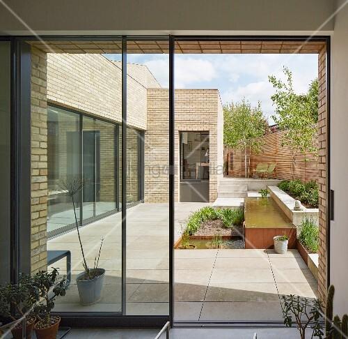 blick auf geometrische terrassengestaltung mit pflanzbeet und wasserbecken eines modernen. Black Bedroom Furniture Sets. Home Design Ideas