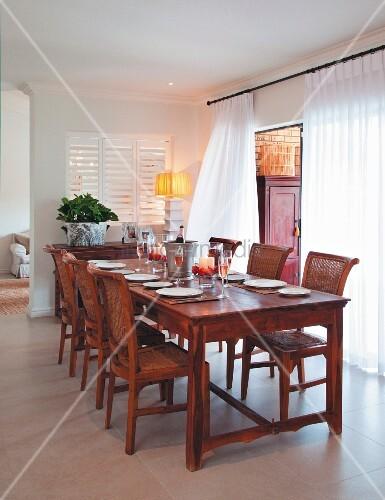 gedeckter esstisch und passende st hle aus r tlichem holz vor fenster mit bodenlangem. Black Bedroom Furniture Sets. Home Design Ideas
