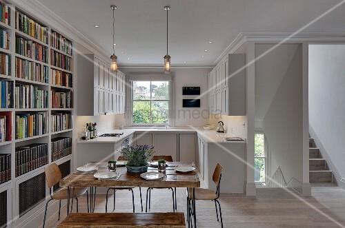 quadratischer rustikaler holztisch mit vintage st hlen und b cherwand im hintergrund weisse. Black Bedroom Furniture Sets. Home Design Ideas