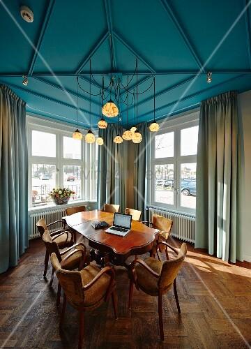 besprechungsraum mit antikem tisch und st hlen unter blau gestrichener decke mit mehreren. Black Bedroom Furniture Sets. Home Design Ideas