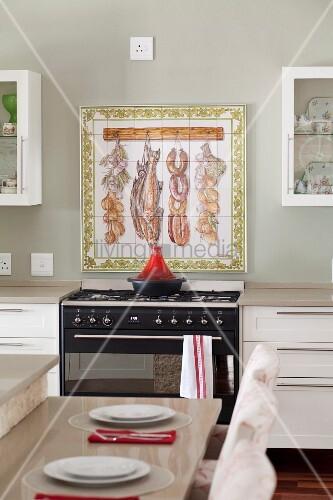 bemalte wandfliesen in rahmen als spritzschutz hinter gasherd vorne der gedeckte thekentisch. Black Bedroom Furniture Sets. Home Design Ideas