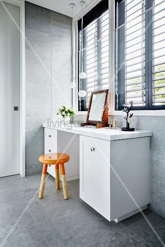 weisser schminktisch und schlichter orangefarbener schemel in dip dye look vor fenster mit. Black Bedroom Furniture Sets. Home Design Ideas