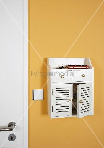 wei es wandschr nkchen neben der t r bild kaufen living4media. Black Bedroom Furniture Sets. Home Design Ideas