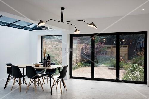 dreiarmige schwarze deckenleuchte und esstisch mit schwarzen schalenst hlen vor terrassent r. Black Bedroom Furniture Sets. Home Design Ideas