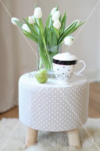 cappuccino und weisser tulpenstrauss auf grauem hocker mit p nktchenmuster bild kaufen. Black Bedroom Furniture Sets. Home Design Ideas