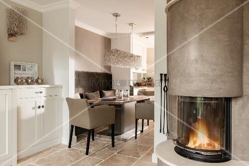 offener wohnraum mit blick auf essplatz seitlich runder kamin bild kaufen living4media. Black Bedroom Furniture Sets. Home Design Ideas