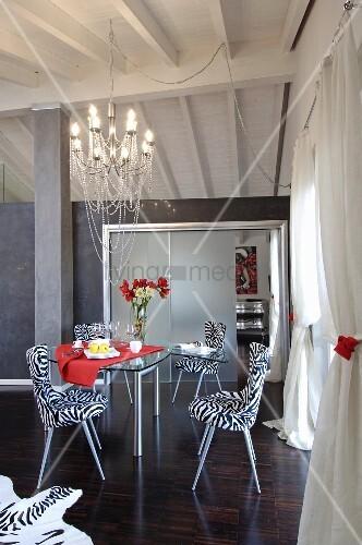 moderne st hle mit zebrabezug um glastisch dar ber kronleuchter in offenem wohnbereich bild. Black Bedroom Furniture Sets. Home Design Ideas