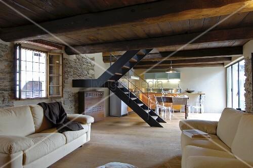 rustikales wohnzimmer mit tiefer holzdecke und natursteinwand im hintergrund treppe und. Black Bedroom Furniture Sets. Home Design Ideas