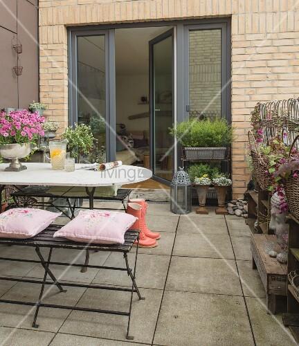 nostalgische kissen auf sitzbank und tisch mit weisser abgerundeter steinplatte auf terrasse. Black Bedroom Furniture Sets. Home Design Ideas