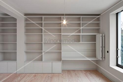 leere minimalistische wei e einbau schrankwand mit regalf chern und klappschiebet ren bild. Black Bedroom Furniture Sets. Home Design Ideas