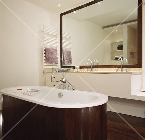 freistehende badewanne mit dunkler holzverkleidung vor minimalistischem waschtisch und spiegel. Black Bedroom Furniture Sets. Home Design Ideas