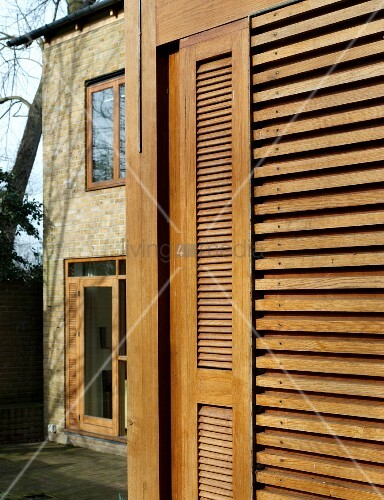 Louvered Shutters Made Of Light Wood On The Facade Of A
