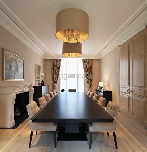 lange tafel mit dunkler oberfl che und gepolsterten st hlen unter h ngelampe mit goldenem schirm. Black Bedroom Furniture Sets. Home Design Ideas