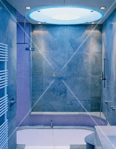 modernes bad mit grauen fliesen an wand und kreisf rmigem deckenlicht ber badewanne bild. Black Bedroom Furniture Sets. Home Design Ideas