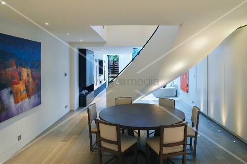 essplatz mit rundem tisch vor geschwungener treppe im modernen raum mit bodenstrahlern im. Black Bedroom Furniture Sets. Home Design Ideas