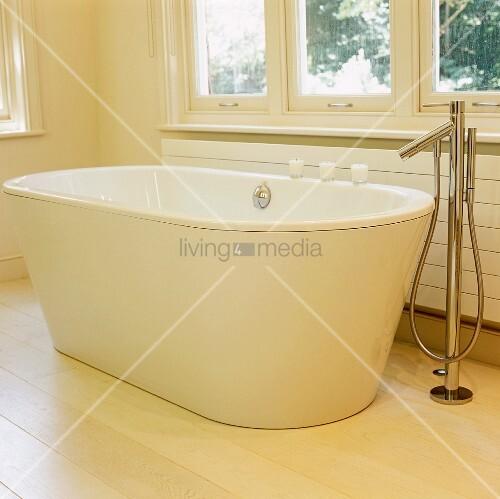 Weisse freistehende badewanne auf hellem dielenboden mit designer standarmatur bild kaufen - Standarmatur freistehende badewanne ...