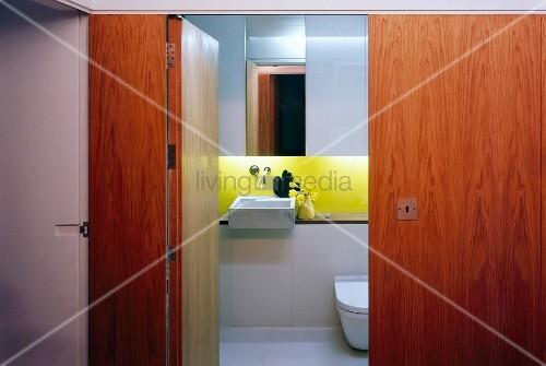 blick durch offene t r aus holz in kleines designtes bad mit waschbecken und gelb lackierter. Black Bedroom Furniture Sets. Home Design Ideas