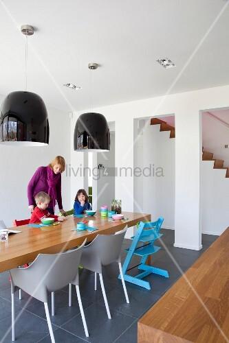 minimalistisches esszimmer mit holztisch und schwarze h ngelampen bild kaufen living4media. Black Bedroom Furniture Sets. Home Design Ideas