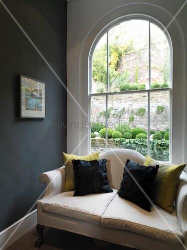 sofa mit kissen vor einem bogenfenster bild kaufen. Black Bedroom Furniture Sets. Home Design Ideas