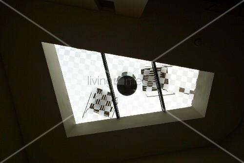 blick durch das dachfenster auf einen runden tisch mit zwei st hlen bild kaufen living4media. Black Bedroom Furniture Sets. Home Design Ideas
