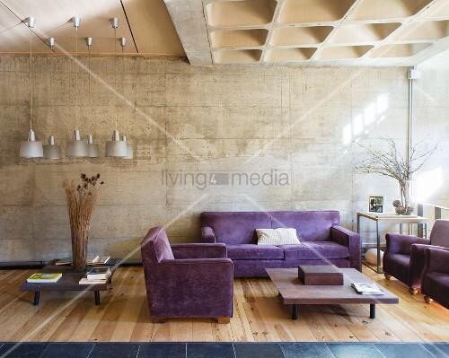 lila sitzgarnitur in einem wohnzimmer mit betonwand und holzboden bild kaufen living4media. Black Bedroom Furniture Sets. Home Design Ideas