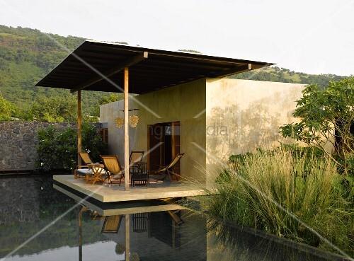 kubisches h uschen mit berdachter terrasse am teich bild kaufen living4media. Black Bedroom Furniture Sets. Home Design Ideas