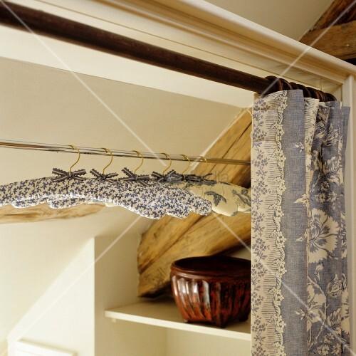 mit stoff bezogene kleiderb gel auf kleiderstange hinter offenem vorhang bild kaufen. Black Bedroom Furniture Sets. Home Design Ideas