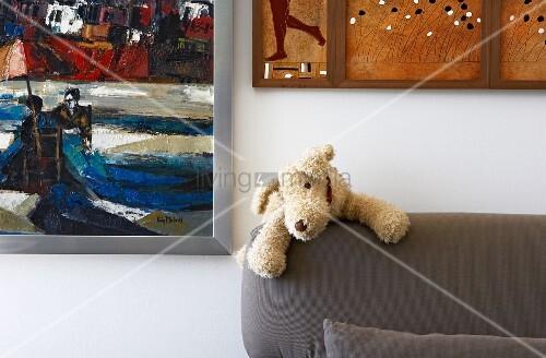 kleiner stoffhund auf der r ckenlehne eines polstersofas und verschiedene gem lde an der wand. Black Bedroom Furniture Sets. Home Design Ideas
