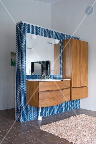 minimalistischer waschtisch und schrank aus holz an blauer mosaikgefliester trennwand im. Black Bedroom Furniture Sets. Home Design Ideas
