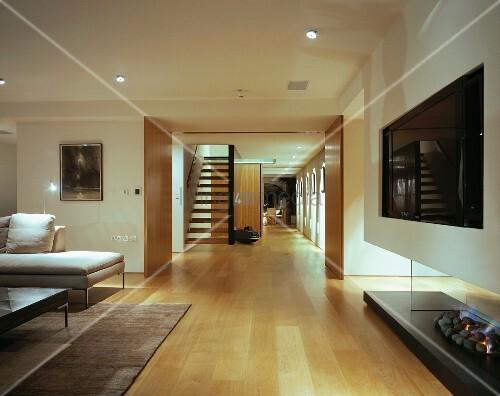 offenes wohnzimmer mit modernem kamin blick auf schwebende holztreppe und schiebeelemente in. Black Bedroom Furniture Sets. Home Design Ideas
