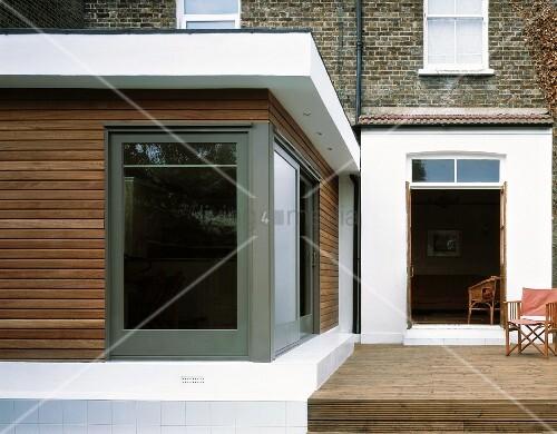 erdgeschossiger moderner anbau mit holzfassade und raumhohem fenster neben terrasse mit. Black Bedroom Furniture Sets. Home Design Ideas
